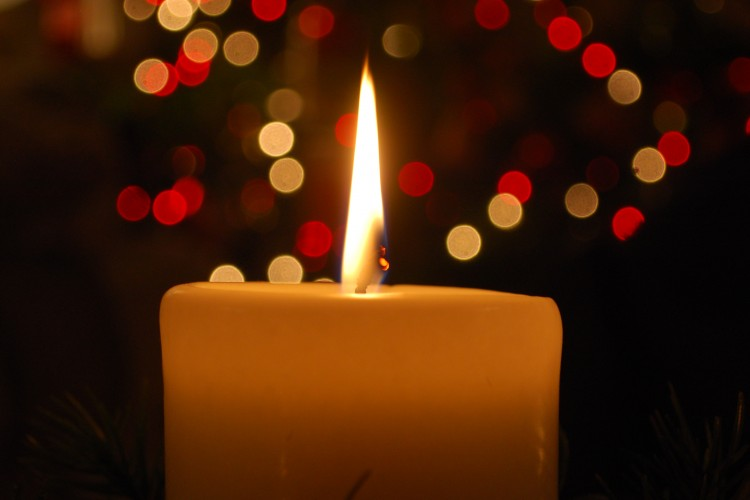 Burning candle, Christmas lights in background blurred